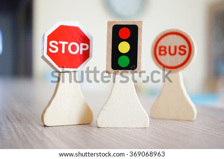 Wooden toy stop sign, traffic lights and bus stop sign - stock photo