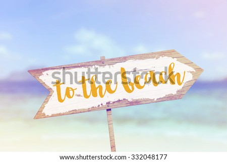 Wooden travel sign against a tropical beach scene - stock photo