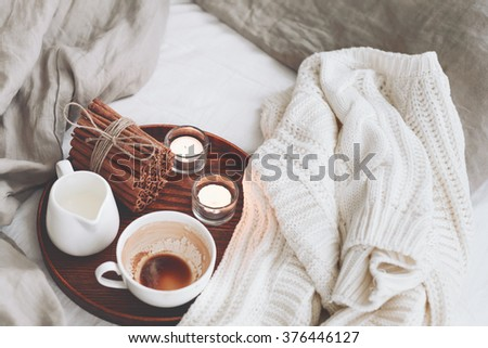 Wooden tray with coffee, milk, cinnamon sticks and tea candles in the bed, lazy morning, warm winter mood - stock photo