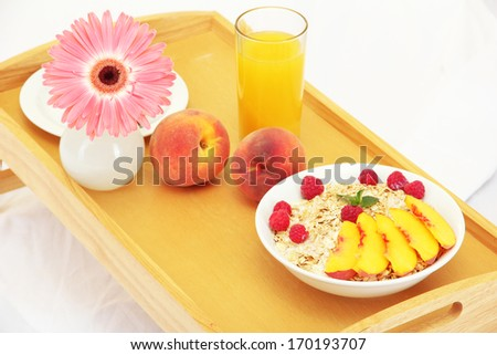 wooden tray with light breakfast on bed, close up - stock photo