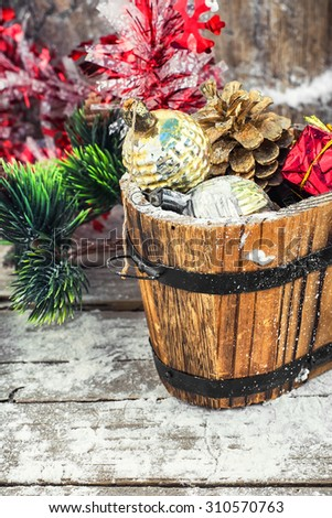 wooden tub with pine cones and Christmas decorations and ornaments. - stock photo