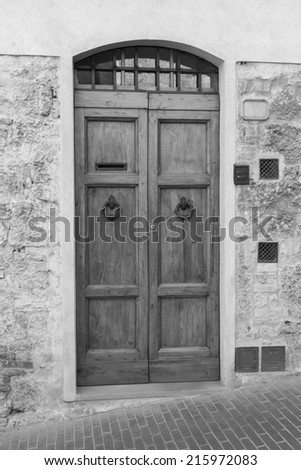 Wooden, Tuscan door in Italy (black and white) - stock photo