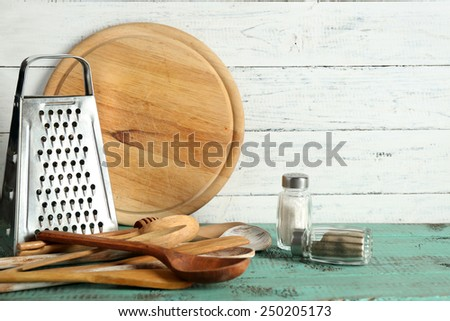 Wooden utensils with metal grater and cutting board on color table and planks background - stock photo