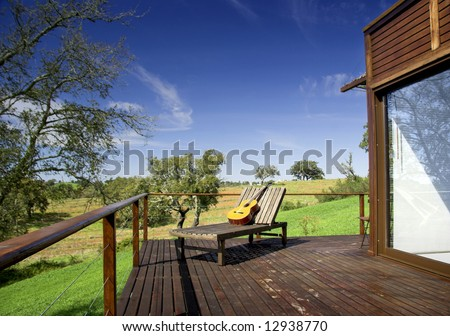 Wooden vacation house with a nice balcony and a long chair with a guitar on top - stock photo