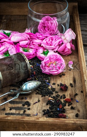 wooden vintage tray with tea brewing,tea strainer and purple buds of the tea - stock photo
