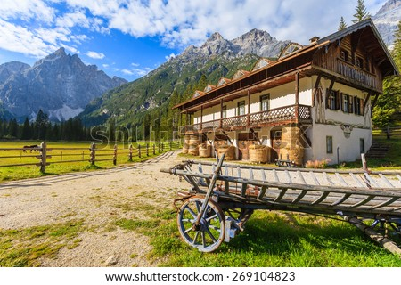 Wooden wagon and green pasture in mountain valley of Fischleintal, Dolomites Mountains, South Tyrol, Italy - stock photo