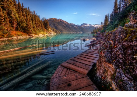Wooden walkway along a scenic mountain lake with sunken logs - stock photo