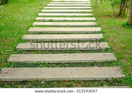 Wooden Walkway in a Lush Tropical Garden - stock photo