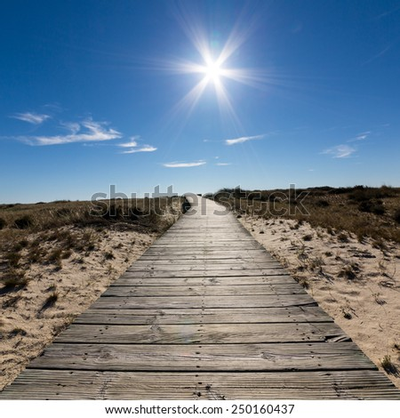 Wooden Walkway Leading to the Beach over Sand Dunes, sunny day - stock photo