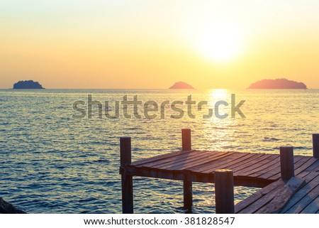 Wooden walkway on the sea coast during sunset. - stock photo