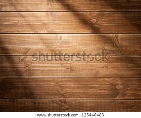 Wooden wall background in a morning light. With shadows from a window frame. - stock photo