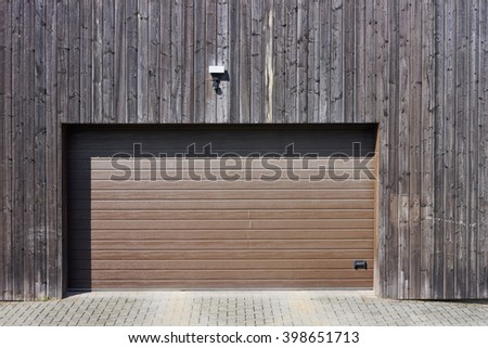 Wooden wall of modern rural garage with the automatic lifted gate. The motion sensor and the alarm system on a wall over an entrance - stock photo
