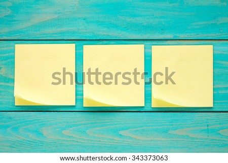 Wooden wall with three blank  sticky notes - stock photo