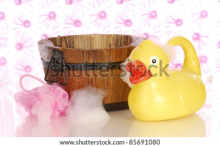 wooden wash tub and rubber duck with soap suds - stock photo