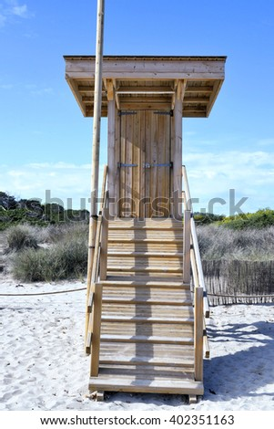 Wooden watch tower on the beach with sand dunes. - stock photo
