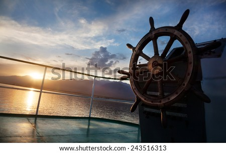 Wooden wheel on the ship at sunset on Issyk Kul lake  - stock photo