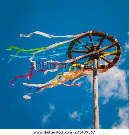 Wooden wheel with bright ribbons on blue sky background. Slavic celebration of Midsummer - stock photo