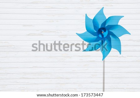 Wooden white shabby background with a blue windmill or pinwheel - stock photo