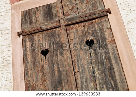 Wooden window shutters with heart shape - Closed old shuttered weathered wooden window in the Alsace, France - stock photo