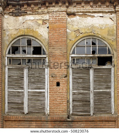 Wooden windows shutters of an old abandoned house - stock photo