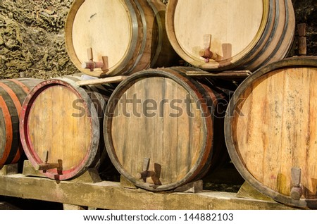 Wooden wine barrels in an underground cellar - stock photo