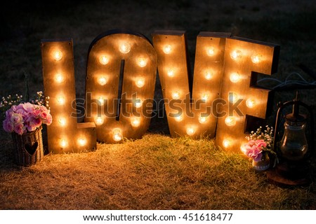 wooden word love with light bulbs and bouquets - stock photo