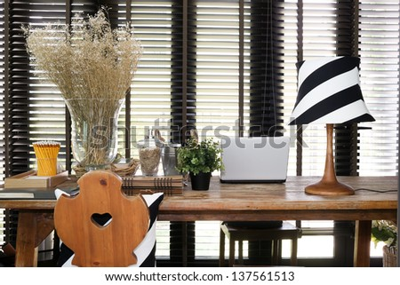 Wooden working table with a laptop, vintage lamp and pillow - stock photo