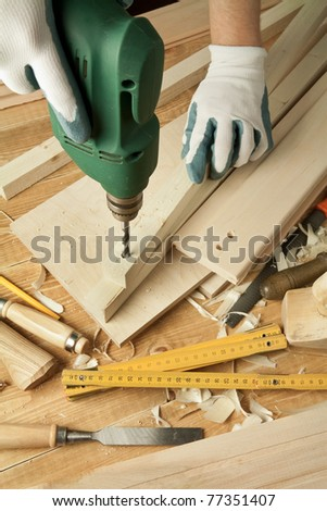 Wooden workshop table with tools. Man's arms drill plank. - stock photo