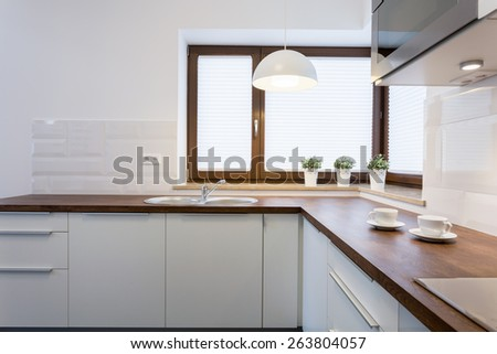 Wooden worktops and white cupboards in luxury kitchen - stock photo