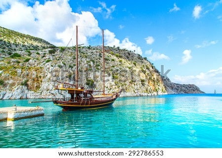 Wooden yacht standing in cosy port on Greek island with clear blue water, Greece - stock photo