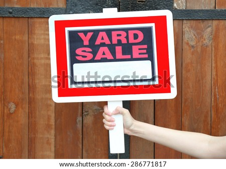 Wooden Yard Sale sign in female hand on wooden fence background - stock photo