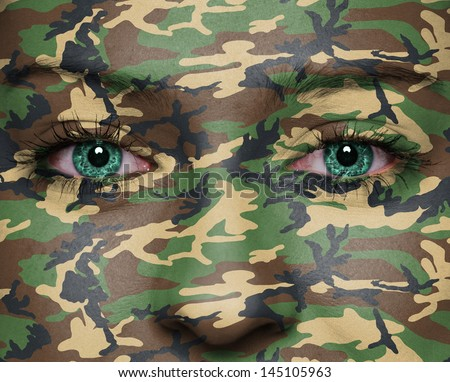 Woodland camouflage painted on woman a face - army concept - stock photo