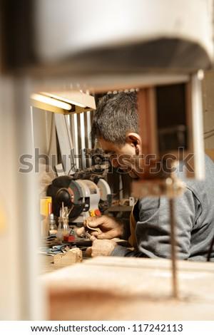 Woodworker making smoking pipe sitting at workbench view through sawing machine - stock photo