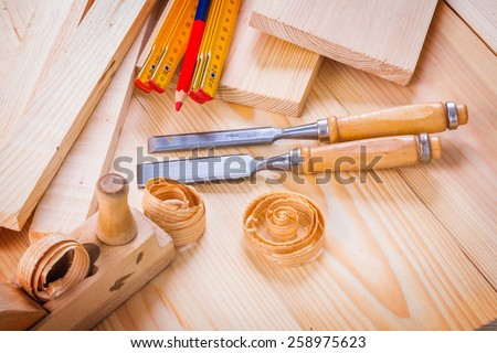 woodworkers plane chisels wooden meter pencil shavings on wooden boards  - stock photo