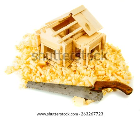 Woodworking. House construction. Joiner's works. The small wooden house, saw and shaving on white background. - stock photo