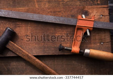 Woodworking or carpentry. Bar clamp and Hammer on rustic piece of wood. Shot in low key and shallow depth of field.  - stock photo