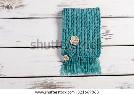 Wool scarf on a wooden background. Knitted handmade scarf. - stock photo