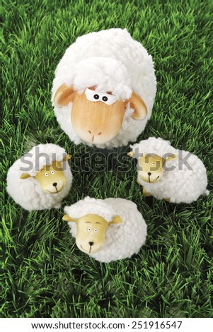 Wool sheep figurines on grass - stock photo