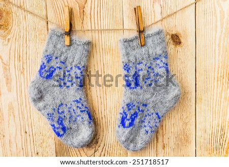 Wool socks hanging on a clothesline on old wooden background - stock photo