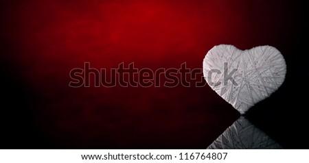 Wool white heart on a dark red background. Valentine's Day. - stock photo