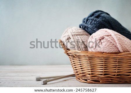 Wool yarn in coils with knitting needles in wicker basket on light blue background - stock photo
