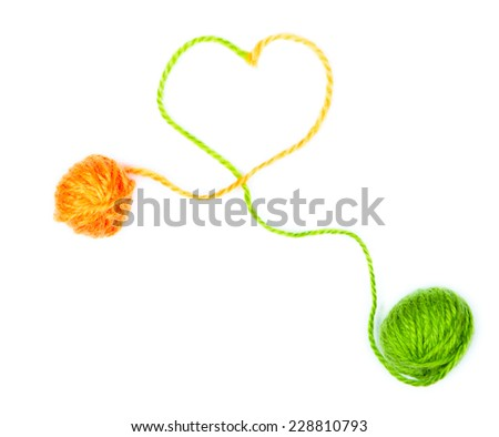 Wool yarn with heart symbol over white background - stock photo