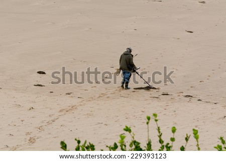 WOOLACOMBE BEACH, DEVON, ENGLAND - OCTOBER 2014: Man with metal detector looking for buried treasure, shown on 22 October 2014 in Woolacombe - stock photo