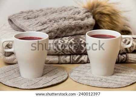 Woolen sweater, knitted hat and two caps of mulled wine - stock photo