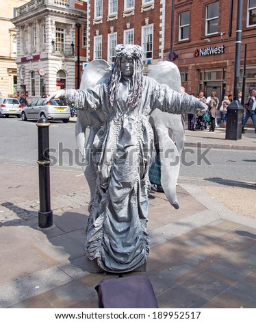 WORCESTER,UK-APRIL 29 2014:Performing street artist posing as an angel statue to earn money on APRIL 29 2014 in Worcester-UK - stock photo