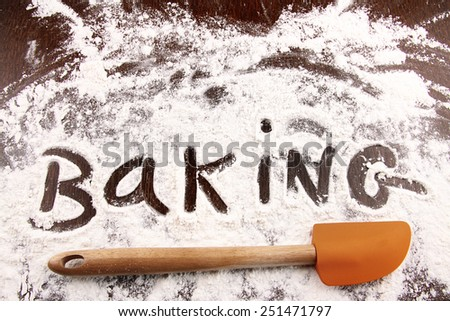 Word baking written in white flour on a wooden table - stock photo