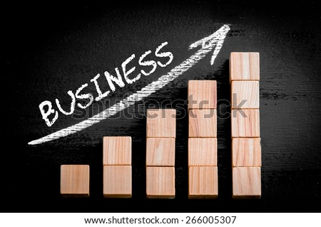 Word Business on ascending arrow above bar graph of Wooden small cubes isolated on black background. Chalk drawing on blackboard. Business Concept image. - stock photo