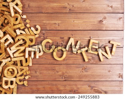 Word content made with block wooden letters next to a pile of other letters over the wooden board surface composition - stock photo