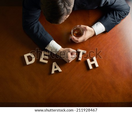 Word Death made of wooden block letters and devastated middle aged caucasian man in a black suit sitting at the table with the glass of whiskey, top view composition with dramatic lighting - stock photo