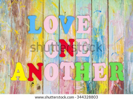 """Word design """"Love one another"""" by colorful letterpress  and red heart  icon on painted wooden  background  - stock photo"""